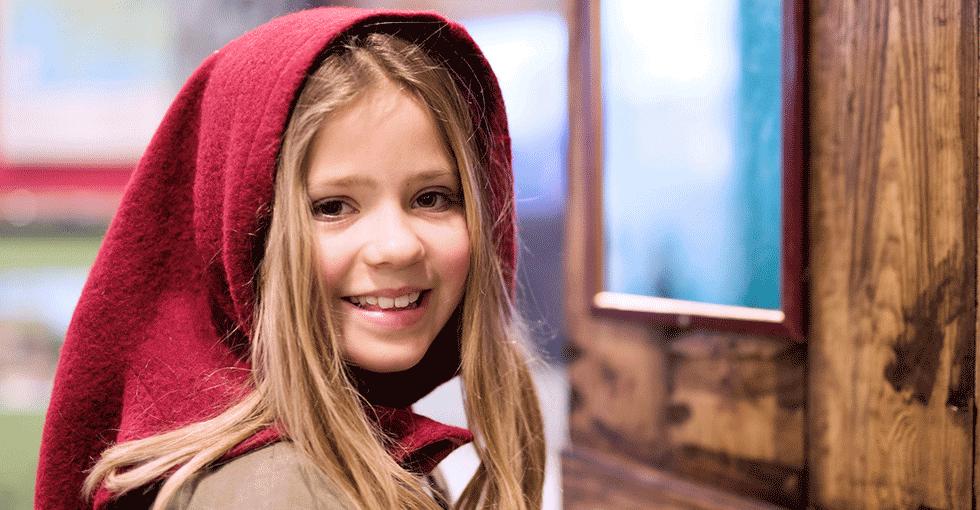 Smilende jente i gammeldags klesdrakt