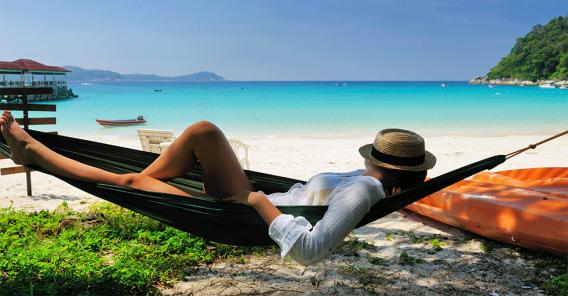 kvinne som slapper av i hengekøye ved stranden
