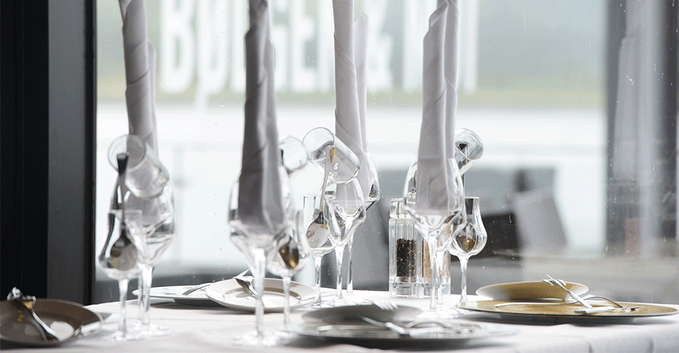 dekket bod med hvite tøyservietter, hvit duk og fine glass