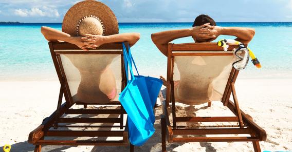 kjærestepar som soler seg i fluktstoler på ei hvit strand