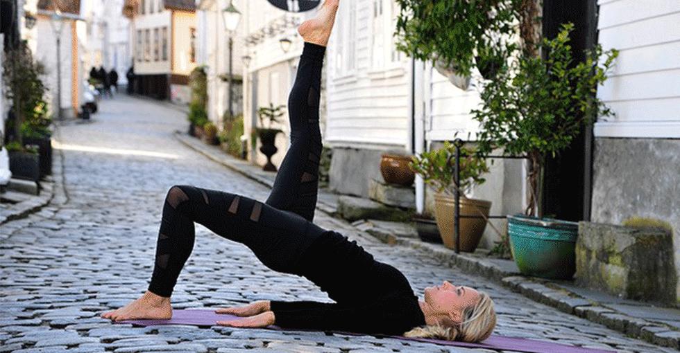 Kvinne som utøver en pilatesøvelse midt i gata