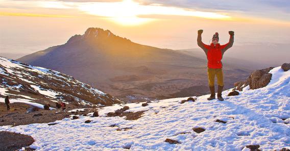 en person på toppen av Kilimanjaro. Sola skinner i bakgrunnen
