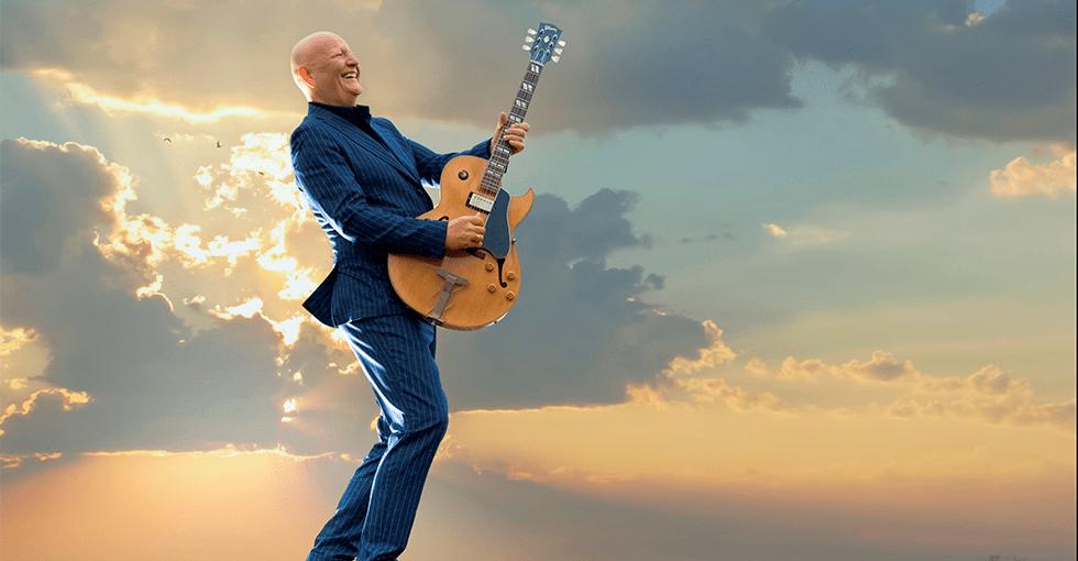 Frode Alnæs på stranden med gitaren