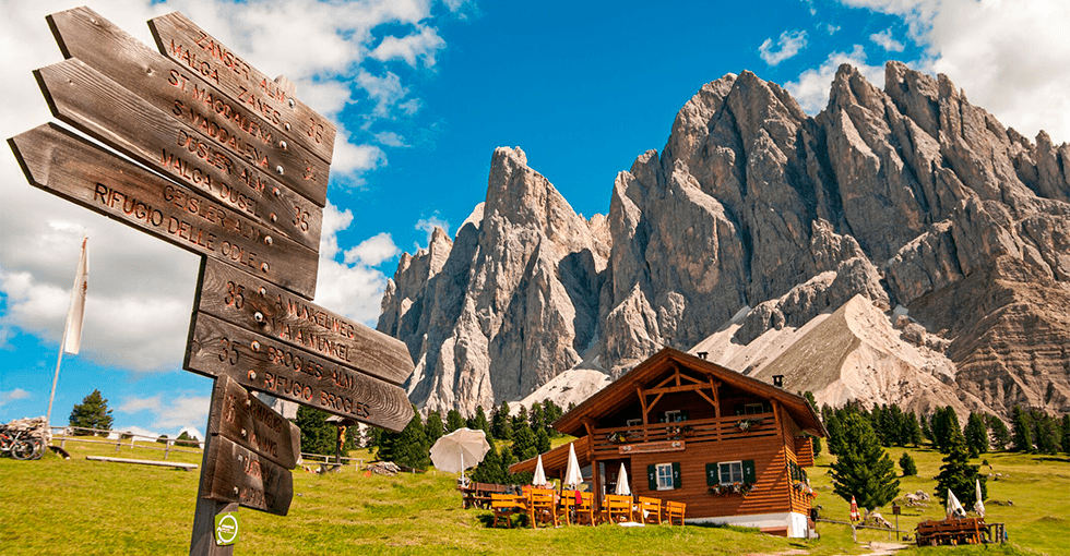 En hytte med Dolomittenen i bakgrunnen