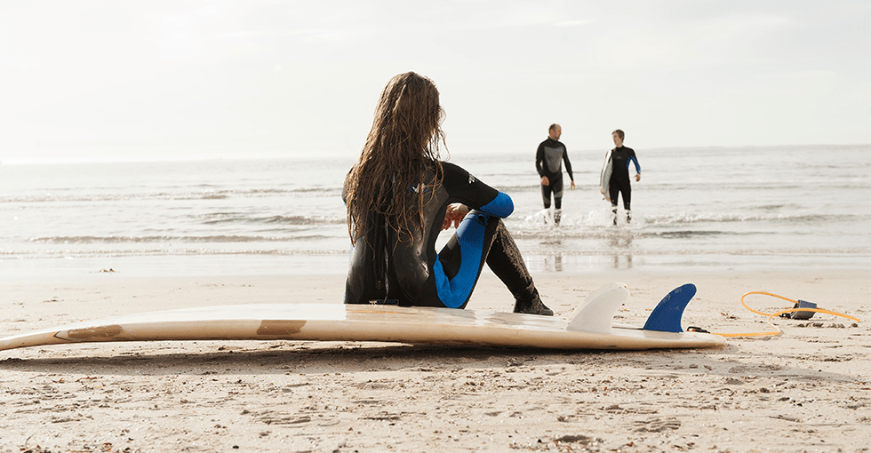 Ung kvinne som sitter på et surfebrett på stranden