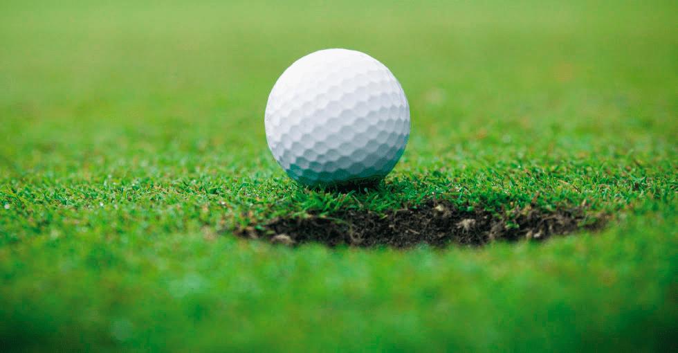 Golfball på grønn, kortklippet plen