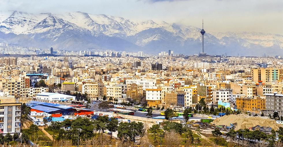 utsikt over tettbebyggelse med bønnetårn og fjell i bakgrunnen