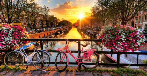 kanal i Amsterdam med to sykler i forgrunnen og solnedgang i bakgrunnen