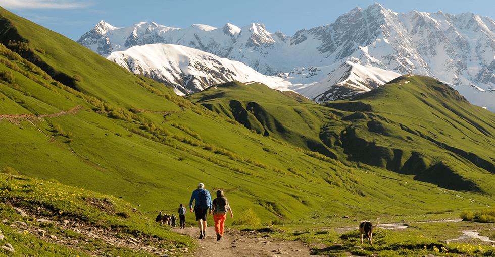 Snødekte fjelltopper i bakgrunnen av folk på tur i sommerklær
