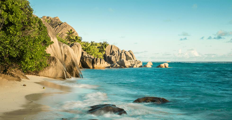 Strand med sandklipper ned mot vannkanten