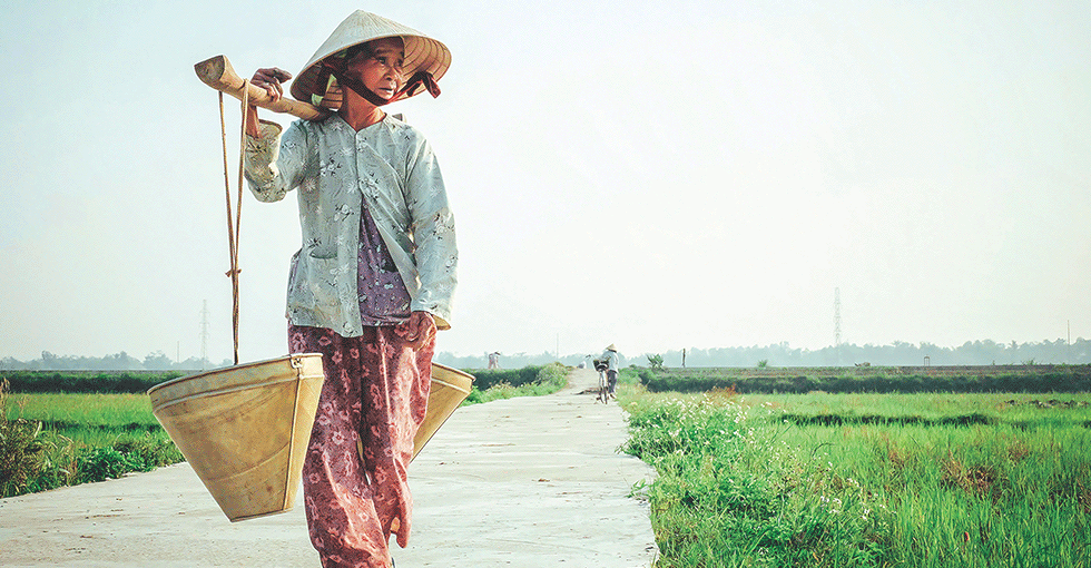 Eldre vietnamesisk kvinne går langs veien